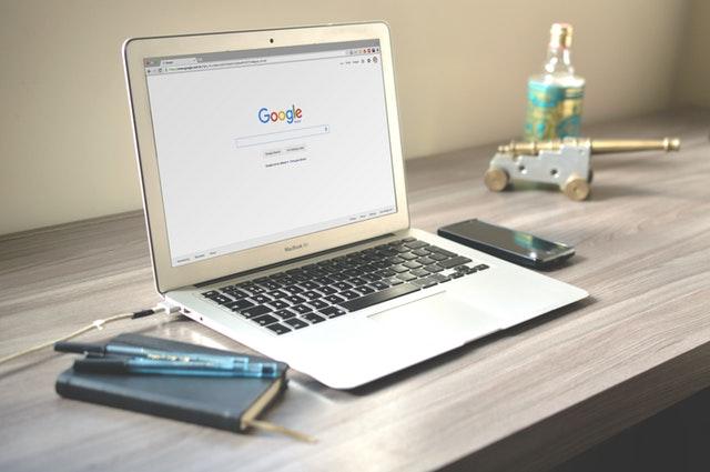 Leistungen für den Erfolg unserer Kunden | Laptop mit Smartphone und Notizbuch auf Schreibtisch